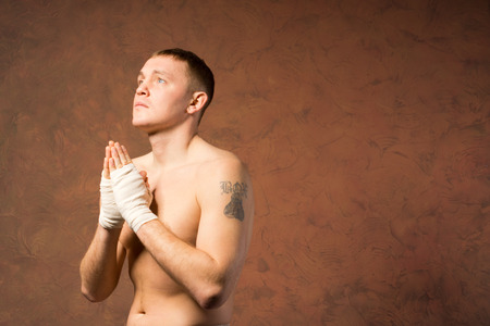 Young boxer praying before a match with his bandaged hands clasped and a serious expression as he prays for a safe victory, with copyspace photo