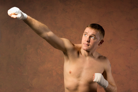 pugilist: Young boxer throwing an upwards punch towards the top left corner of the frame with his bandaged fist and a look of determination