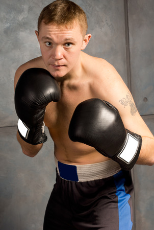 pugilist: Professional young boxer in a fight crouching forwards with his fists raised watching for an opening to strike his opponent