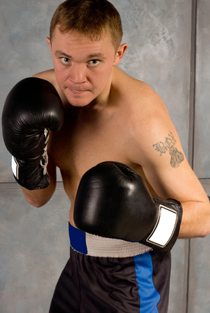 Determined professional young boxer in training leaning in ready to land a punch on his opponent, close up view photo
