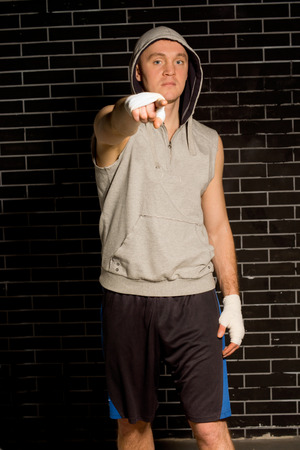 identifies: Young boxer standing in darkness against a brick wall pointing at the camera with his bandaged hand as he shows or identifies someone or draws your attention to something Stock Photo