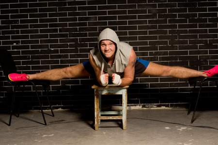 supple: Fit supple young boxer working out balancing on three stools with his legs doing the splits to tone and strengthen his muscles and increase his agility in the ring