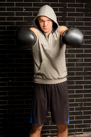 pugilist: Young boxer punching with both of his gloved fists towards the camera with a look of determination during a workout in a gym
