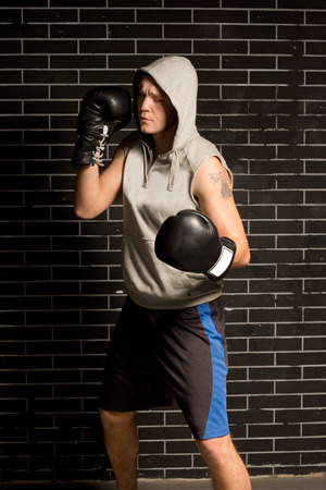 pugilist: Young boxer working out during training standing in front of a dark brick wall with his gloved fists raised and a look of concentration on his face