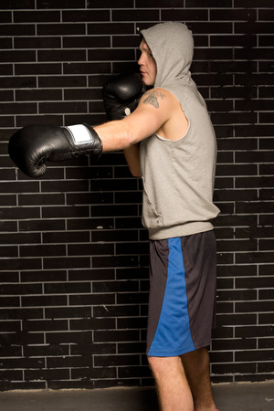 short sleeved: Fit muscular young boxer wearing a short sleeved hoodie working out against a brick wall throwing a punch with his gloved hand