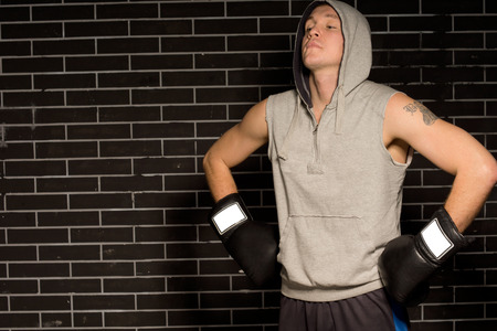 pugilist: Young boxer doing breathing exercises before a fight standing with his gloved hands on his hips and head tilted back in the darkness with copyspace