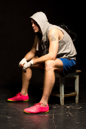 Bored young boxer waiting for his match sitting on a wooden stool in a hoodie with his gloves dangling round his neck, side view against a dark  photo