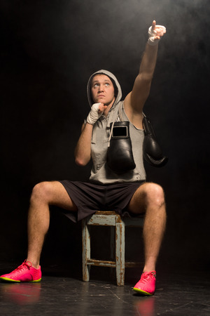 pugilist: Boxer sitting waiting on a wooden stool in a darkened corner pointing to heaven as he psyches himself up before a fight asking for help to win the match