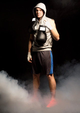 pugilist: Grim looking boxer determined to win standing staring at the camera with his gloves dangling around his neck as smoke wafts around his legs