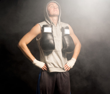 pugilist: Young boxer doing breathing exercises to calm himself and increase his concentration before a fight standing with his hands on his hips and head tilted back with closed eyes