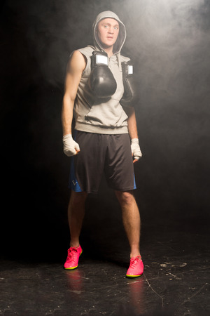 Muscular young boxer preparing for a fight standing in smoke filled darkness with his gloves slung around his neck and bandaged fists clenched photo