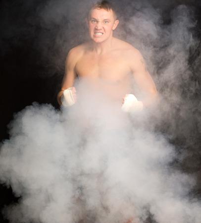 pugilist: Media boxeador joven y ambicioso joven gru�endo a la c�mara sobre el humo flotando mientras est� de pie con los pu�os vendados plantearon