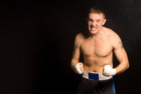 gritting: Angry determined young boxer gritting his teeth with clenched bandaged fists on a dark with copyspace