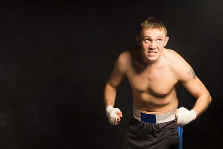 pugilist: Resolute young boxer with a grim determined expression coming towards the camera out of the shadows, with copyspace