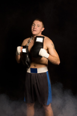 Muscular fit young boxer preparing for a fight standing in the darkness with his gloves slung round his neck and bandaged hands looking at the camera photo