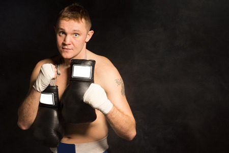 Serious resolute young boxer standing staring at the camera with his bandaged fists raised and his gloves slung around his neck, dark with copyspace photo