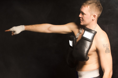 Side view of a fit young boxer standing pointing with his bandaged hand in the darkness with his gloves hanging around his neck photo