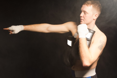 Muscular young boxer pointing with his bandaged hand extended in front of him as he stands with his other fist raised and his gloves dangling around his neck, side view on a dark  photo