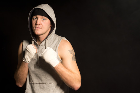 resolute: Serious resolute young boxer in a hoodie standing watching the camera intently with his bandaged fists raised to his chest Stock Photo