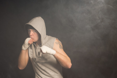 hooded top: Muscular boxer ready for a fight standing with his fists raised looking out intently from under his hooded top as he watches his opponent carefully against a dark with copyspace