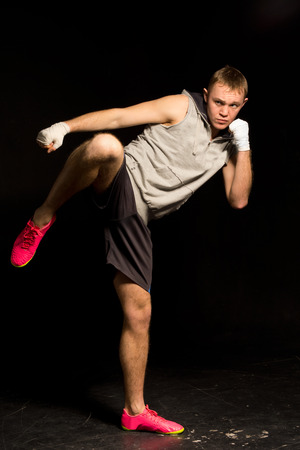 pugilist: Athletic young kickboxer kicking out during a fight balancing on one foot as he readies himself to follow up with a punch from his bandaged fist