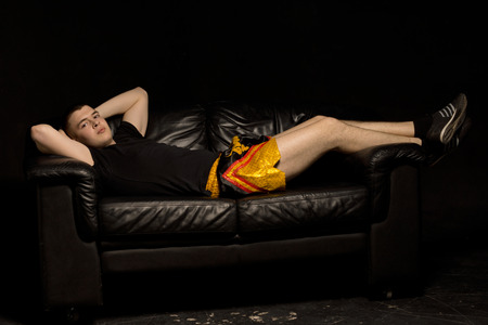Fit handsome young athlete relaxing on a black sofa in darkness in gold shorts lying with his hands behind his head looking at the camera photo