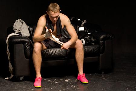pugilist: Boxeador que se prepara para una pelea de vendar las manos mientras se est� sentado en una silla de cuero i la oscuridad con sus guantes junto