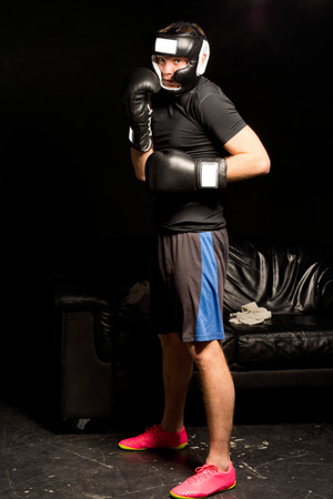 pugilist: Young boxer waiting to enter the ring standing in his gloves and helmet in a watchful stance in a dark environment