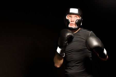 Low angle view of a determined young boxer with his fists at the ready carefully watching every move of his opponent as he waits for the opportunity to attack, with copyspace photo