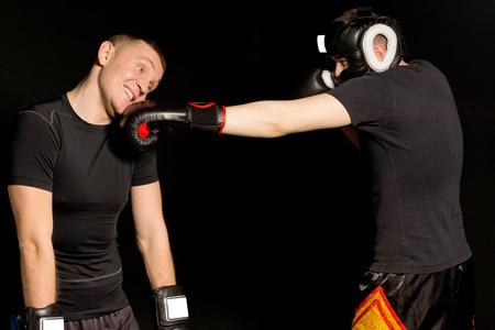 pugilist: Boxer aterrizaje de un golpe sobre sus oponentes mand�bula mientras los dos hombres se pelean en el ring durante el partido en el oscuro