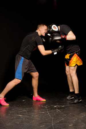 opponents: Two young boxers sparring in the ring during a training session as the one goes in for a low blow punch to his opponents abdomen Stock Photo