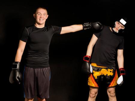 agachado: Los dos boxeadores jóvenes engañando alrededor junto con el uno de pie frente a la cámara con una sonrisa mientras la perforación de reojo a su amigo que está esquivando fuera del camino