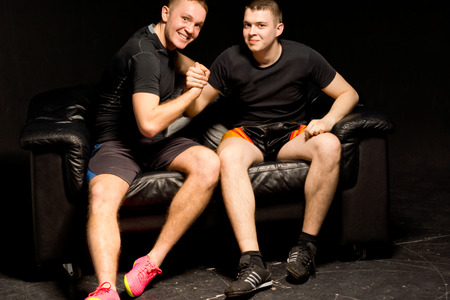 pugilist: Two happy fit young men having a friendly arm wrestle as they sit together on a black leather couch in the darkness