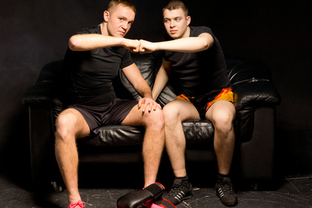 pugilist: Two young boxers giving each other a high fives of congratulations after a successful training session together in the ring as they sit on a black leather couch in darkness