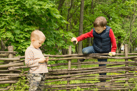 other side of: Young boy climbing over a rustic wooden fence in rural woodland as his friend stands waiting for him on the other side Stock Photo