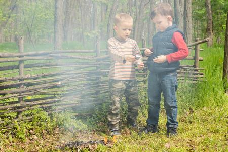fend: Due giovani ragazzi giocano insieme a un fuoco di fumare che hanno costruito e illuminato in un lussureggiante campeggio verde campagna come imparano a badare a se stessi