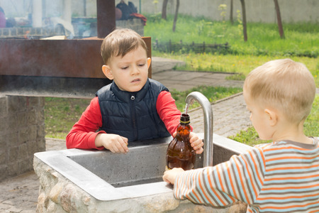 Two young boys filling a bottle of water from a running tap over a stone sink at a campsite photo