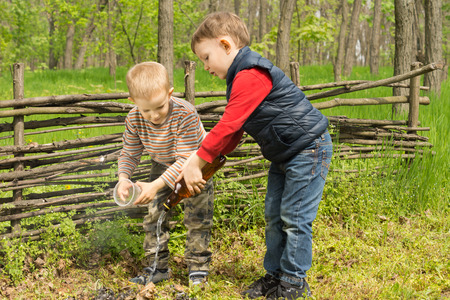 dampen: Two responsible little boys putting out a fire that they lit while playing in a grassy field wetting it down with water to ensure that the hot embers are properly extinguished