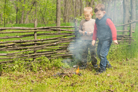 Proud little boys standing watching a burning fire that they have lit in a rural field while out on a camping vacation