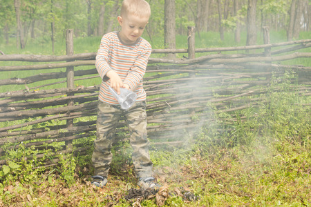 dampen: Little boy trying to extinguish a fire at a campsite pouring a container of water onto it resulting in a cloud of smoke