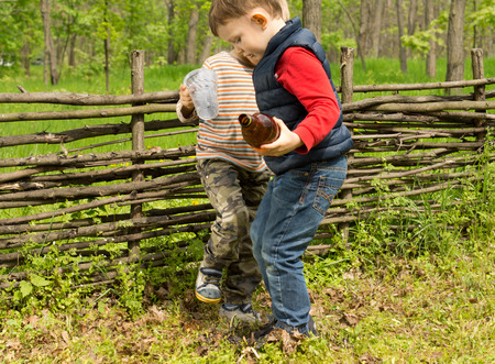 dampen: Two small boys stamping out a fire in a grassy field alongside a rustic fence after they have extinguished it with water from the bottles they are carrying to ensure that it is safe to leave