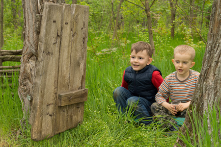 squatting down: Two cute playful young boys squatting down in the long green grass looking through an open dilapidated old wooden gate between two trees in woodland grinning with happiness as they enjoy the outdoors