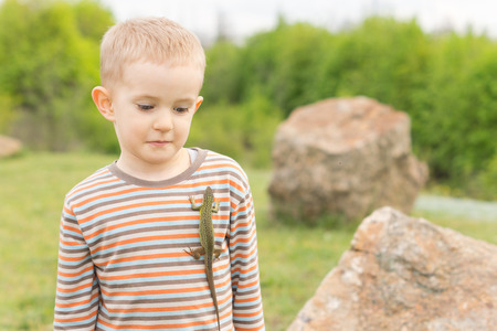 unafraid: Cute little blond boy with a lizard on his chest looking down at it with uncertainty as he stands in a rocky rural park Stock Photo