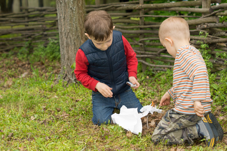 squatting down: Two small boys trying to light a fire in a field squatting down in front of a pile of dead leaves, wood and paper with a box of matches Stock Photo