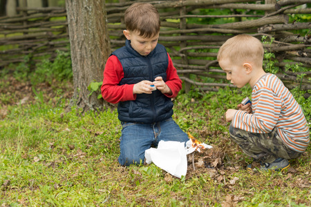 squatting down: Two young boys lighting a fire outdoors as they play together in a garden or park squatting down in the grass setting fire to leaves, twigs and paper