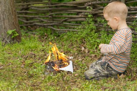 kindling: Little boy playing with fire squatting down on the ground in front of a pile of burning twigs and leaves, side view