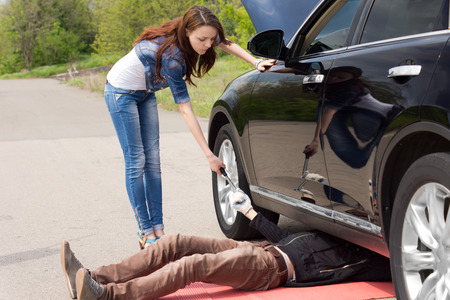 breaking down: Woman driver watching a mechanic fix her car after breaking down at the side of a rural road handing him a socket spanner as he works under the engine compartment