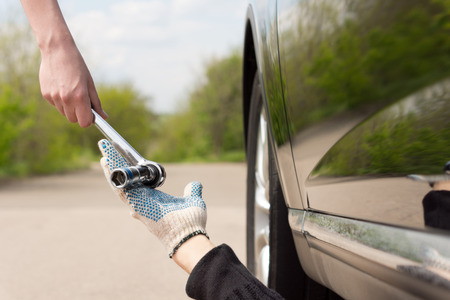 Woman handing a socket wrench or spanner to a mechanic working underneath her car after it has broken down at the side of a rural road