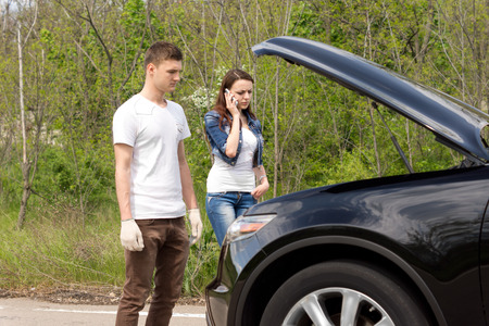 Young couple phoning for roadside assistance after their car has broken down standing looking into the engine compartment with the bonnet up photo