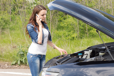bonnet up: Beautiful young woman driver calling for breakdown assistance as she stands in front of her car with the bonnet up looking at the engine on a rural road Stock Photo
